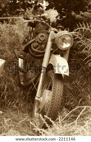 classic old motorcycle in parked in countryside - stock photo