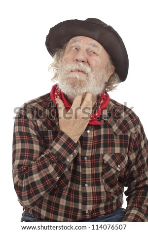 Classic Old West style cowboy with battered felt hat looks sideways and scratches whiskers. Isolated on white, vertical, copy space. - stock photo