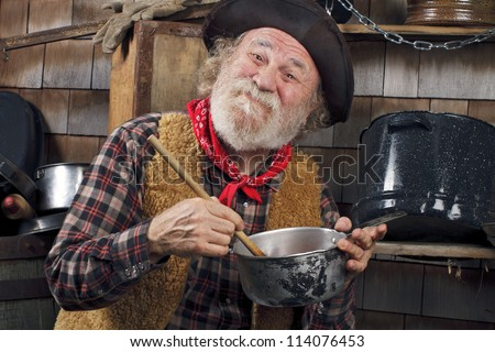 Classic Old West style cowboy with felt hat, grey whiskers, red bandana. He stirs a saucepan with a wooden spoon. Camp cookware and wood shingles in background. - stock photo