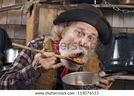 Classic Old West style cowboy with felt hat, grey whiskers, red bandanna. He sits and eats beans from a saucepan. Camp cookware and wood shingles in background. - stock photo
