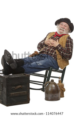 Classic old west style friendly cowboy with felt hat, grey whiskers, revolver. He leans back in a rocking chair with feet up. Isolated on white, vertical, copy space. - stock photo