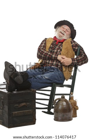 Classic old west style laughing cowboy with felt hat, grey whiskers, revolver. He leans back in a rocking chair with feet up. Isolated on white, vertical, copy space. - stock photo