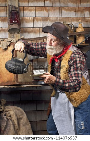 Classic old western style cowboy cook with felt hat, grey whiskers, apron. He is ready to pour tea into a white china tea cup. - stock photo