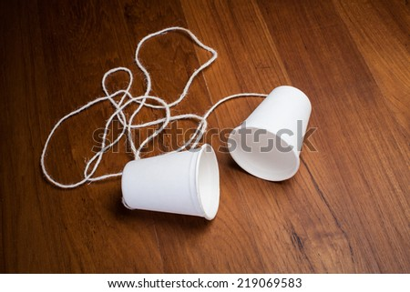 classic paper cup phone on wood background - stock photo