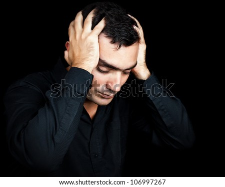Classic portrait of an hispanic man suffering a strong headache or depression pressing his forehead with his hands isolated on black - stock photo