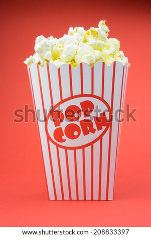 Classic retro box popcorn on red background  - stock photo