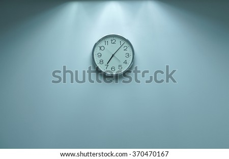 Classic round wall clock on the wall background. - stock photo