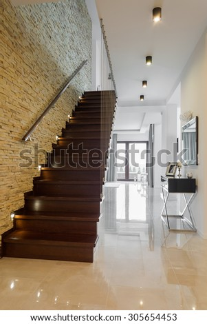 Classic style hallway with marble floor and wooden stairs - stock photo