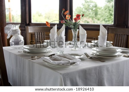 Classic table setting with white tablecloth, napkins and red flowers - stock photo