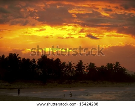 Classic tropical sunset and family playing in the ocean and waves. - stock photo