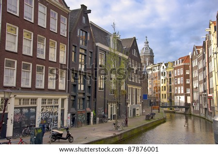 Classic view of Amsterdam. View from the canal to the city against the blue sky. Urban landscape in Amsterdam. - stock photo
