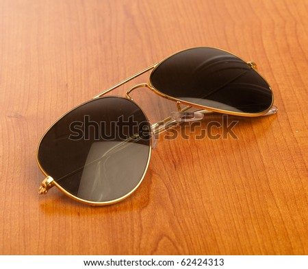 classic vintage sunglasses on a wooden table - stock photo