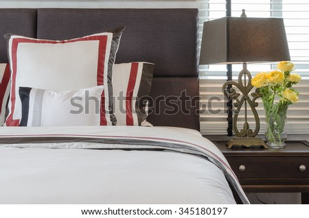 classic white bed with pillows and classic lamp style on table side at home - stock photo