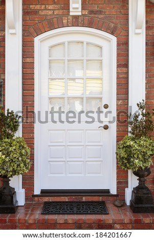 Classic white door to brownstone home. Door is framed by white home detail, a doormat, and two plants.  - stock photo