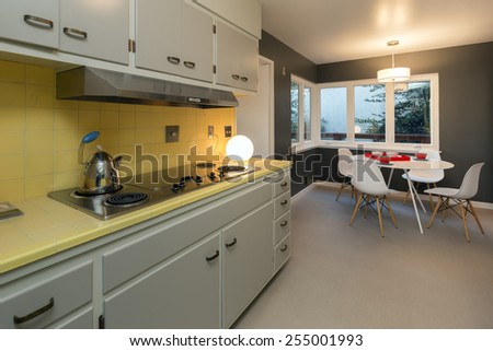 Classic white yellow kitchen with Breakfast nook in chocolate brown with white designer chairs, orange dishes, dishware and table. - stock photo