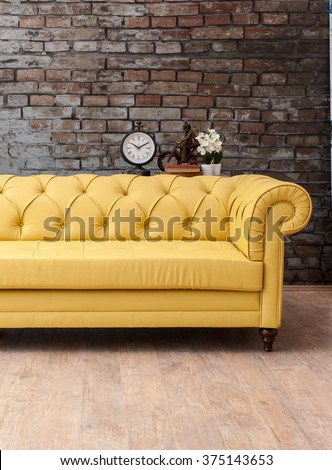 classic yellow sofa living room with brick wall and clock  - stock photo