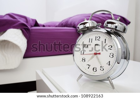 classical alarm clock on bedside table - stock photo