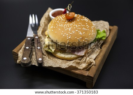 Classical American fresh juicy burger with chicken and ham on a wooden tray with a spicy chili sauce. Beautiful photo on a dark background. - stock photo