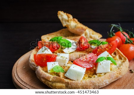 Classical frisella tomato, cheese mozzarella and basil. Italian starter friselle. Dried bread called freselle on wooden board. Italian food. Healthy vegetarian food. Antipasti. Selective focus. - stock photo
