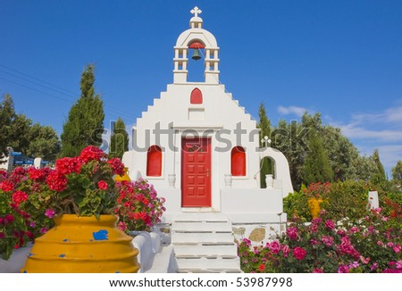 Classical Greek architecture of the churches on the islands. White Church, surrounded by flowers in the garden and colorful pots ... - stock photo