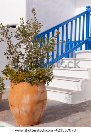 Classical Greek white staircase with a pots of flowers - typical architecture in Islands - stock photo