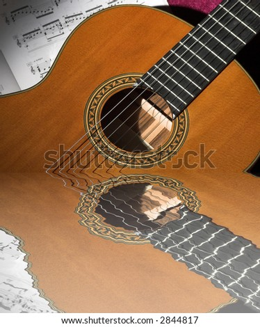 Classical guitar detail under spotlight with reflection in water - stock photo