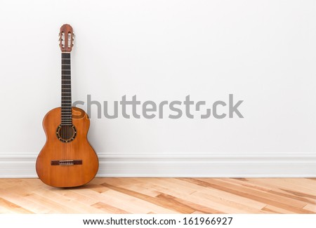 Classical guitar in an empty room, with copy space. - stock photo