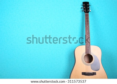 Classical guitar on blue wallpaper background - stock photo