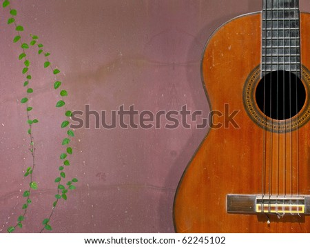 Classical guitar with nylon strings on grunge wall - stock photo