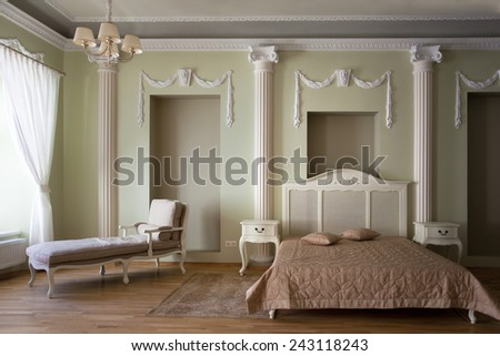 Classical interior of bedroom with a queen size bed and a couch at the window - stock photo