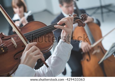 Classical music symphony orchestra string section performing, female violinist playing on foreground, hands close up - stock photo