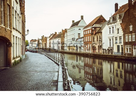 Classical old houses at water canal in european city. Bruges (Brugge), Belgium. Image used vintage tone filter. - stock photo