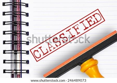 Classified rubber stamp on the note book - stock photo
