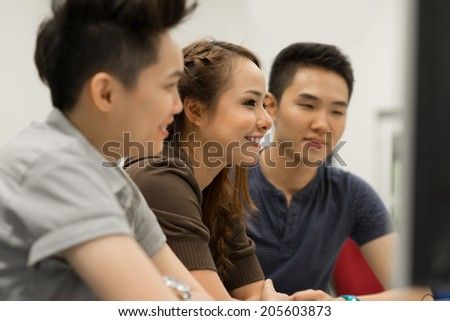 Classmates looking at the computer screen during the class, side view - stock photo