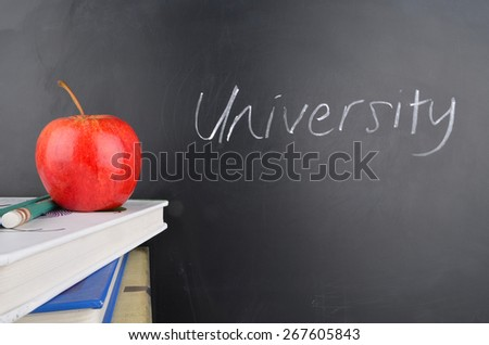 Classroom with red apple,books and handwriting in white chalk on blackboard - stock photo