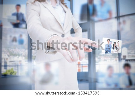 Classy businesswoman presenting coworkers pictures on digital interface - stock photo