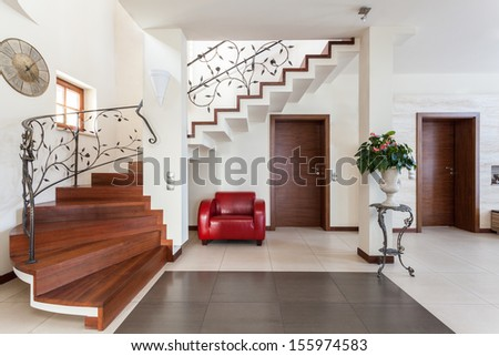 Classy house - Corridor with elegant stairs and armchair - stock photo