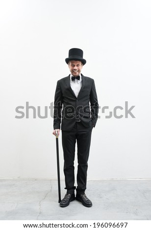 Classy smiling gentleman standing on white background and concrete floor in elegant suit with cane and bowler hat. - stock photo