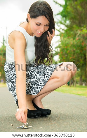 Classy woman wearing fashionable skirt and elegant black high heels bending down to pick up keys from asfalt surface, green park background - stock photo
