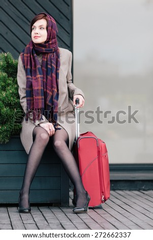 Classy woman with suitcase is waiting for someone - stock photo
