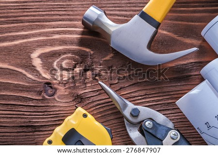 Claw hammer blueprints nippers and tape-measure on wood board construction concept  - stock photo