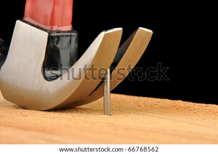 Claw hammer pulling out nail - stock photo