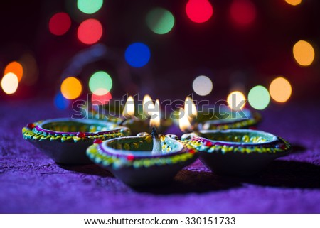 Clay diya lamps lit during Diwali Celebration. Greetings Card Design Indian Hindu Light Festival called Diwali.  - stock photo