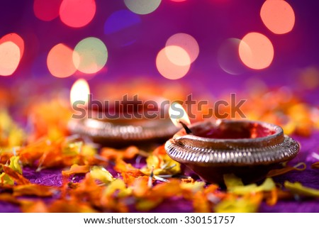 Clay diya lamps lit during Diwali Celebration. Greetings Card Design Indian Hindu Light Festival called Diwali.  - stock photo
