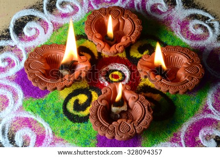 Clay diya lamps lit during diwali celebration, Rangoli in background - stock photo
