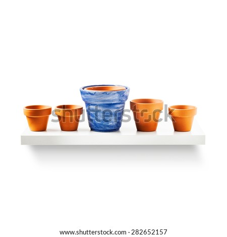 Clay flower pots in a row on shelf isolated on white background. Garden equipment. Group of objects with clipping path - stock photo