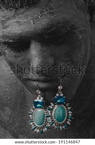 clay mask on the face of a man on the lips earrings - stock photo