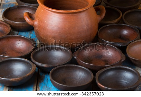 clay pot and dishes on old wooden blue background - stock photo