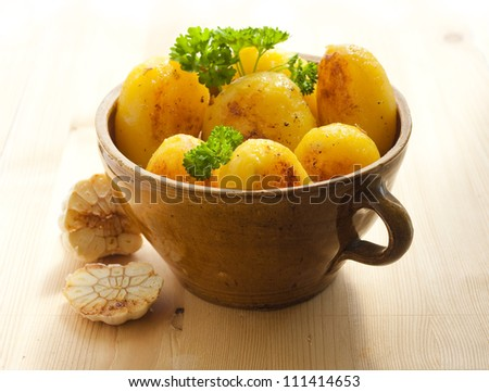 Clay pot full of potatoes and a head of garlic on the wooden table. - stock photo