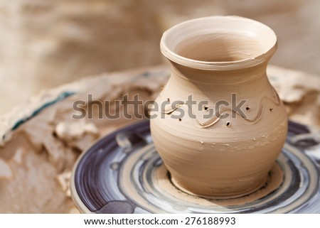 Clay pot with pattern on a pottery wheel - stock photo